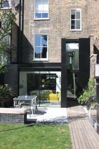 This rear extension in Dalston incorporates a full glass roof, frameless windows, minimally framed aluminium doors and aluminium cladding.