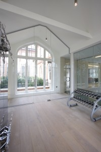 Frameless internal glazing against a backdrop of a traditional timber, arched window