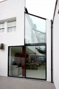 Black back painted glass covers the steel support above sliding door for a sleek glass facade