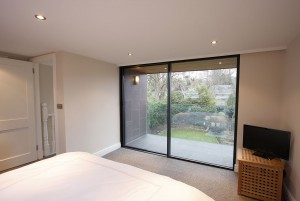 Slim framed sliding doors lead from a loft conversion bedroom to small balcony