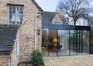 minimal sliding doors into a glass box extension to a listed home.