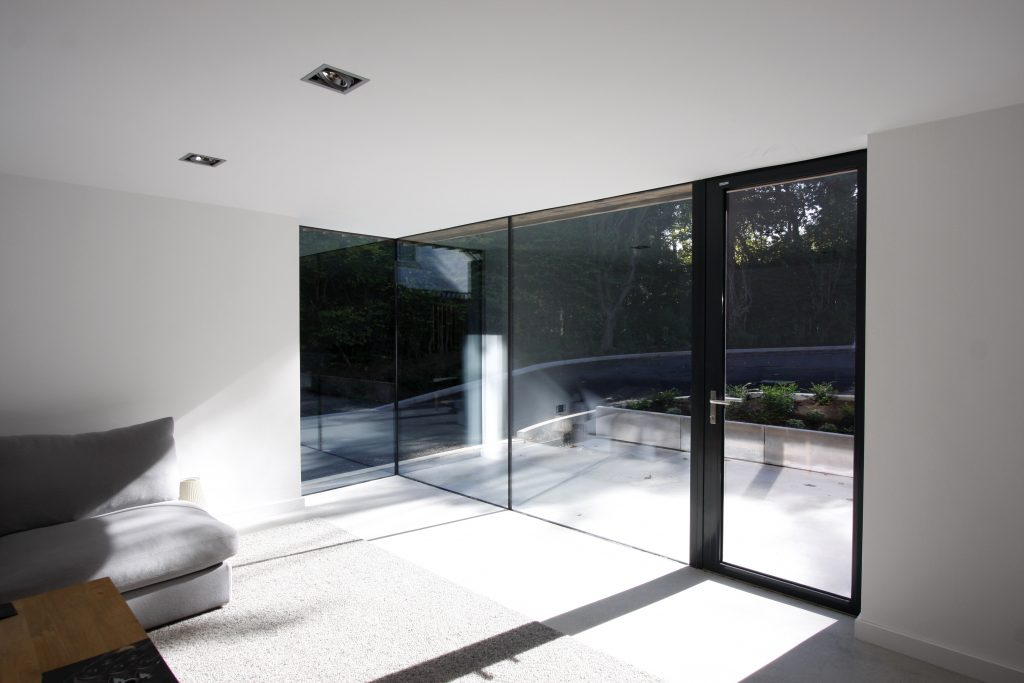 An aluminium casement door within a structural glass wall. Edge Hill, Newcastle.