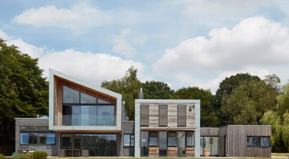 La Madonnina, a contemporary new build home featuring large walls of frameless and slim framed aluminium windows overlooking the countryside. The lower sections feature large sliding glass doors.