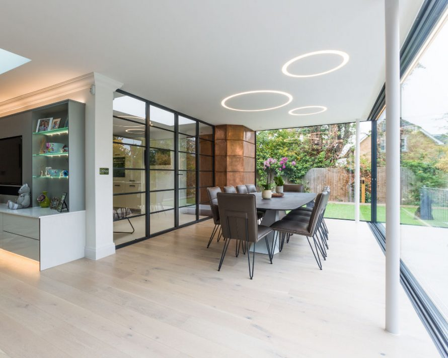 An open plan, brightly lit contemporary dining space surrounded by minimal glass sliding doors connecting to the garden outside