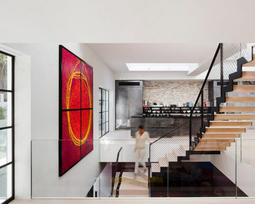 An artistic studio conversion into a contemporary home, featuring a central wooden staircase lined with frameless glass balustrades. The surrounding living spaces are characterised by structural glass floors and steel framed doors and windows