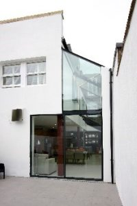 Modern glass side infill extension with minimal windows sliding glass door and glass overlight