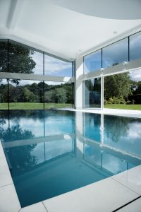 Indoor swimming pool with heated minimal glass walls