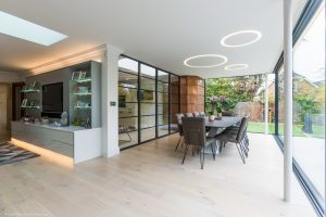 Contemporary open plan dining area in a modern glass walled extension with steel glass partition