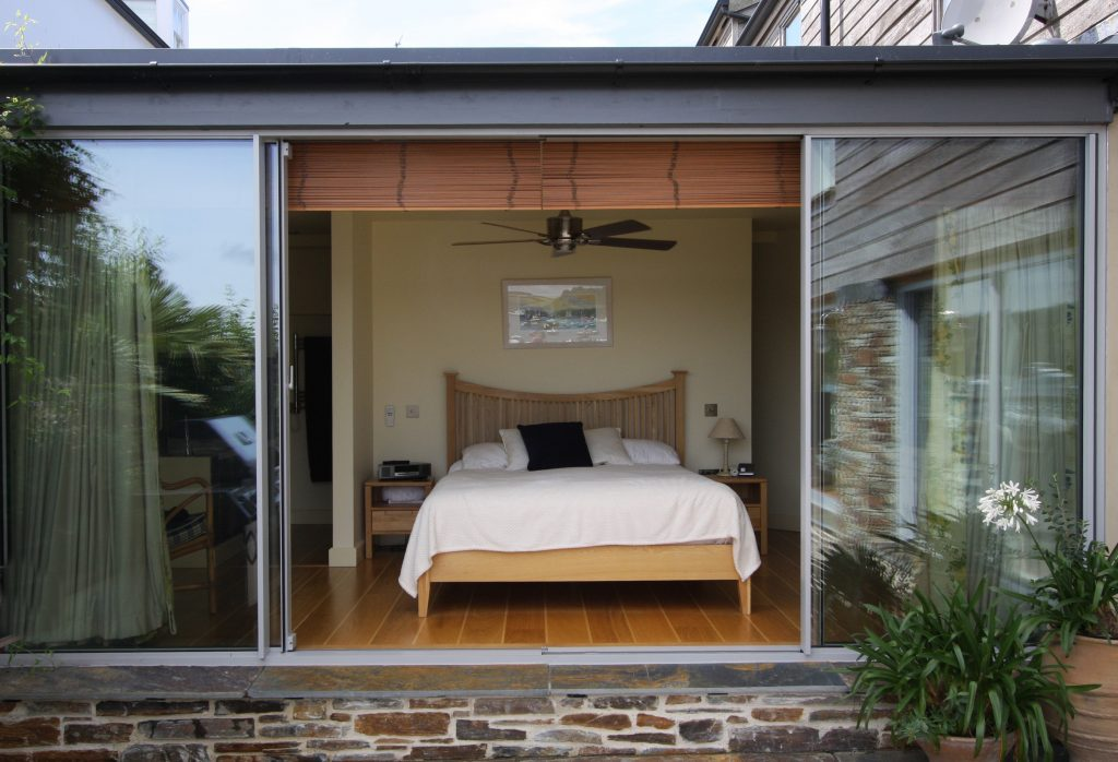 Contemporary bedroom with sliding glass door with sound reduction