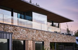 floor to ceiling windows leading onto an external balcony with a frameless glass balustrade