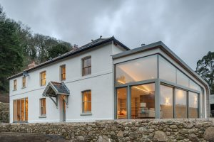 Glass box extension to farmhouse with sliding glass doors