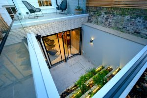 Basement renovation with glass doors leading onto sunken garden courtyard