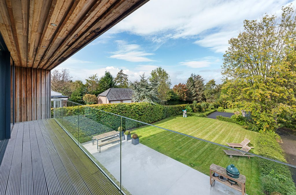 balcony with glass balustrades overlooking manicured lawn