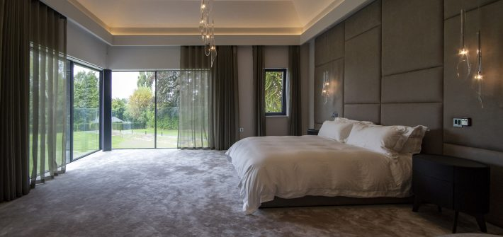 Contemporary bedroom with concealed curtain track over glass walls