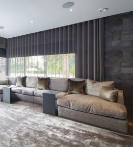 Contemporary sofa space with concealed curtains over glass walls