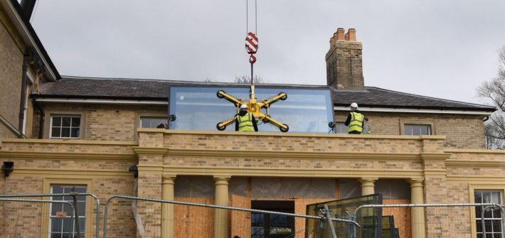 crane lifting flat roof glazing pane in a glass installation